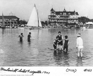 The building on the right is the Hanlan Hotel in 1907. The building on the left is the Toronto Rowing Club.