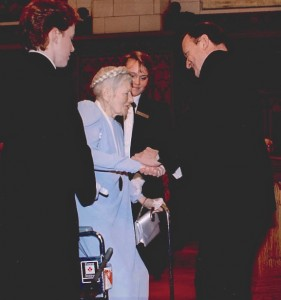 A frail but typical (coronet braids, wrist purse, gloves, diamonds) Margaret Hyndman receiving the Persons Award from the Speaker of the Senate (1988) Status of Women Canada/ National Archives